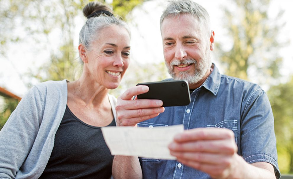 A middle aged couple doing a mobile deposit using their smartphone