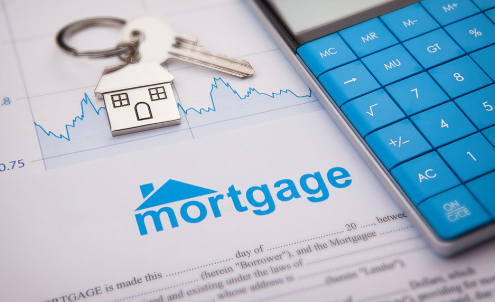 House keys and a calculator on top of mortgage papers